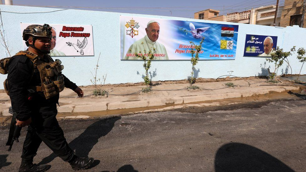 An Iraqi policeman walks next to posters of Pope Francis outside the St Joseph Chaldean Catholic Church in Baghdad's Karada district, Iraq (3 March 2021)