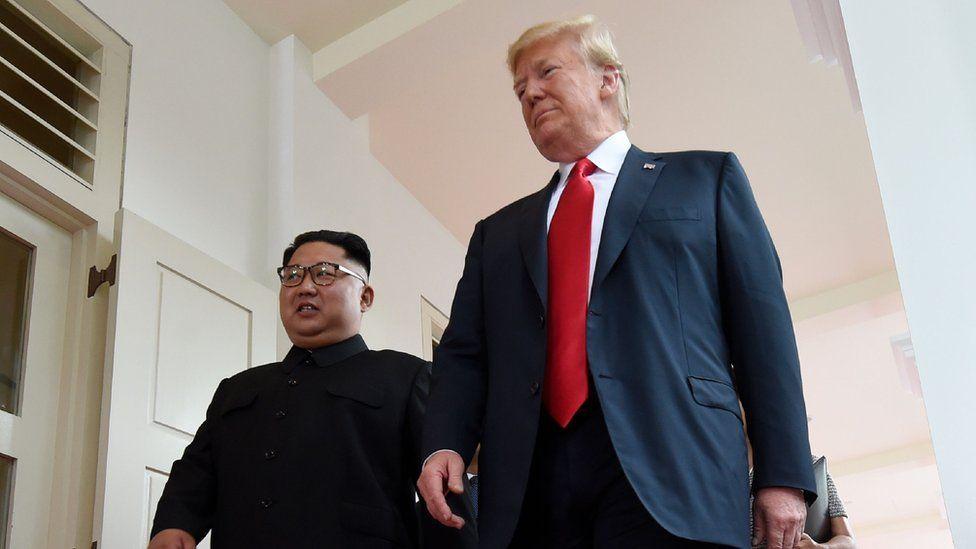 "North Korea""s leader Kim Jong Un (L) walks with US President Donald Trump (R) at the start of their historic US-North Korea summit"