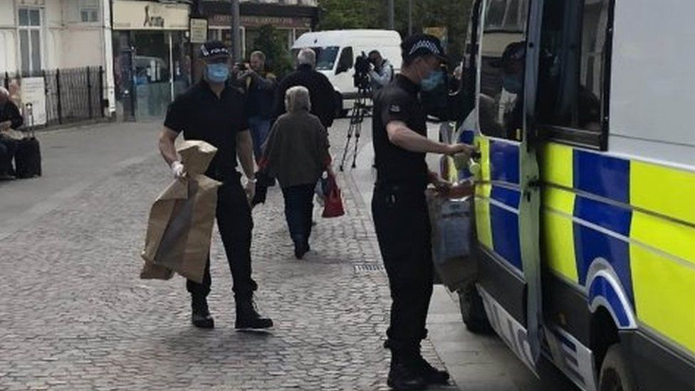 Police carrying evidence bags outside the cafe