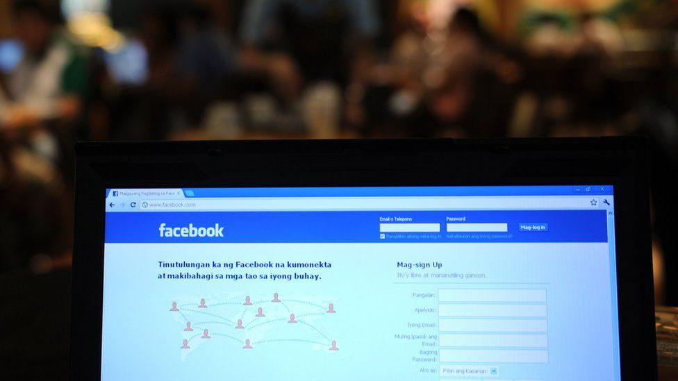 A coffee shop employe walks past a display showing the Tagalog language version of social networking site facebook in Manila on May 15, 2012