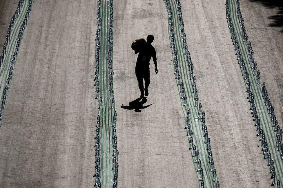 A Muslim volunteer walks past long rows of plastic bottles.