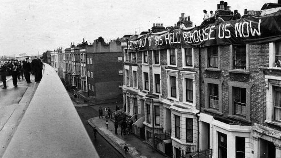 A banner saying 'Get Us Out Of This Hell Re-house Us Now' flies over a group of homes when the 'Westway' in London was opened.
