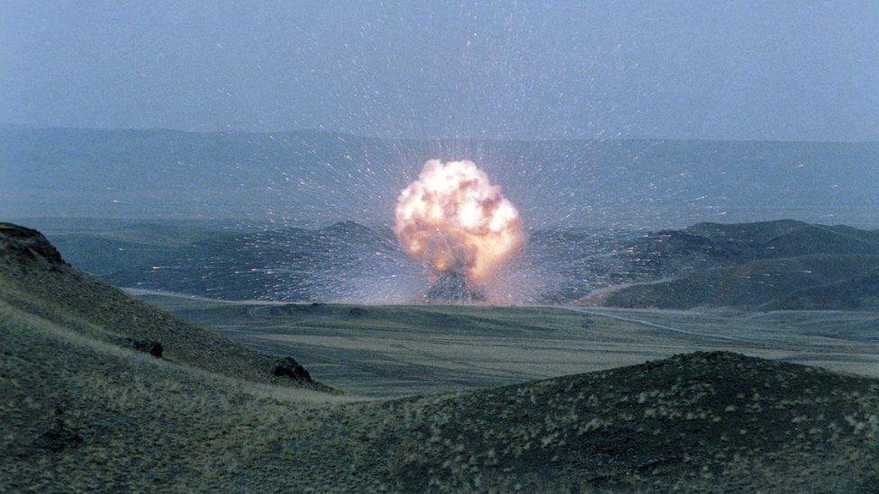 An explosion in a huge open plain of rolling green fields