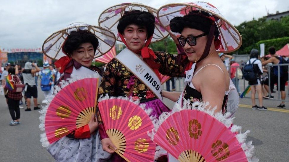 Three men in traditional Taiwanese female dress in Taipei on 29 October