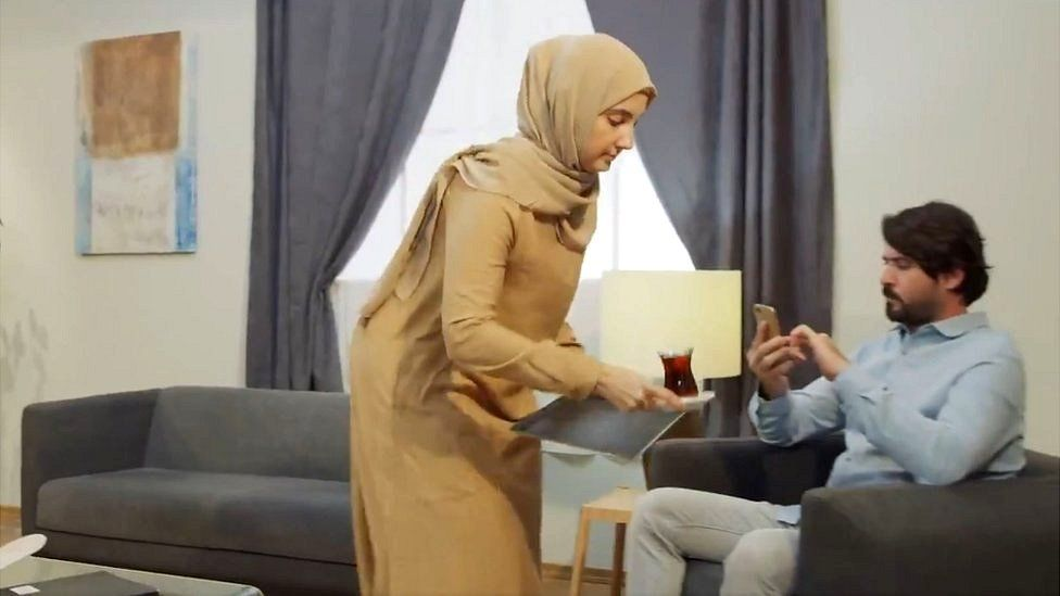 Scene from video showing woman serving tea to husband as he looks at his phone