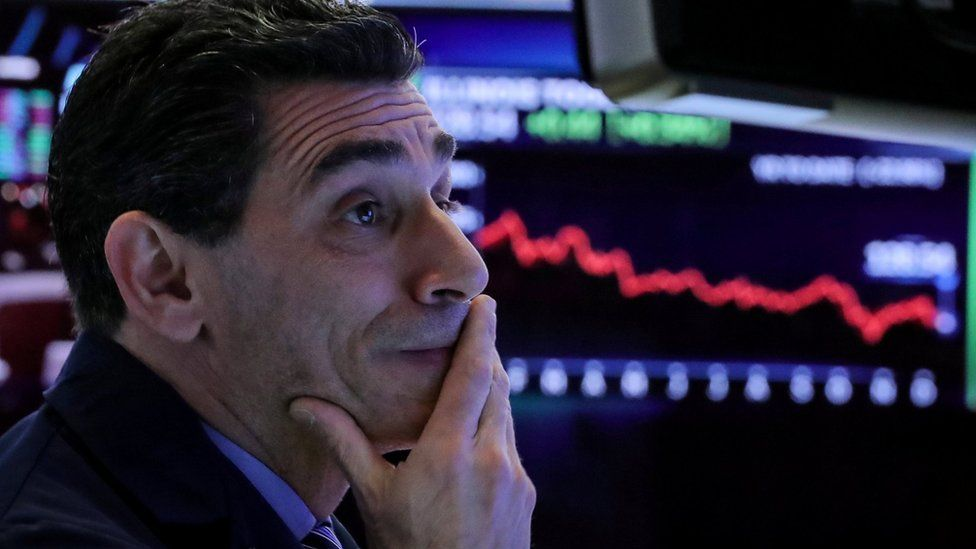 A trader works at his post on the floor of the New York Stock Exchange