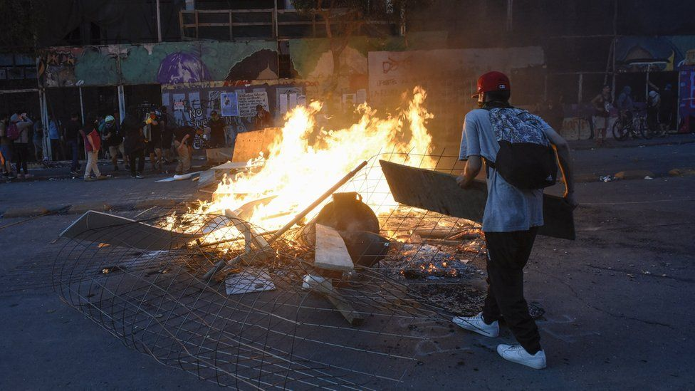 A demonstrator makes a burning barricade during a national strike and general demonstration called by different workers' unions on 12 November, 2019 in Santiago, Chile.