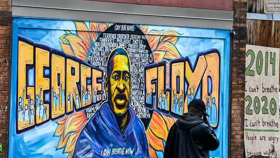 A man walks past the mural of George Floyd
