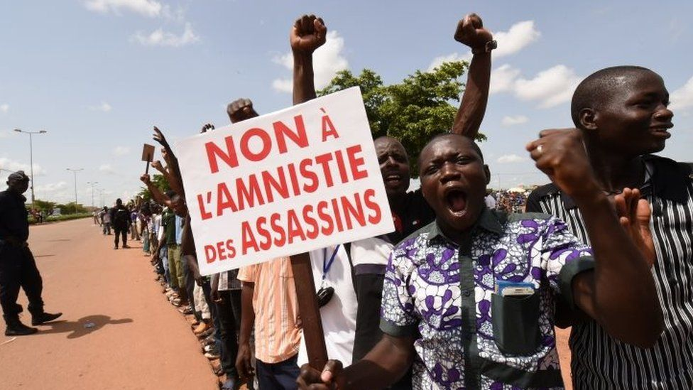 """Protesters shout slogans while holding a sign reading """"No to an amnesty for assassins"""" during a demonstration not far from the hotel where Ecowas leaders were holding a meeting in Ouagadougou on 23 September 2015"""
