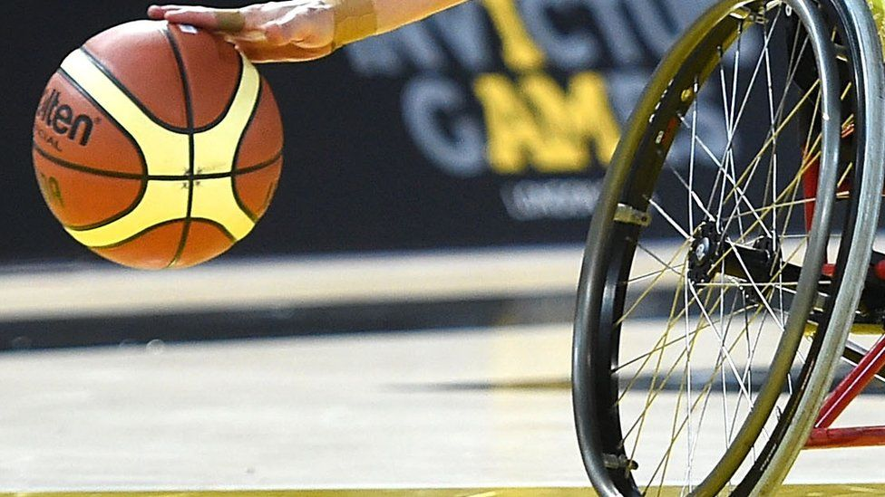 A cropped image showing a basketball and the wheel of a wheelchair