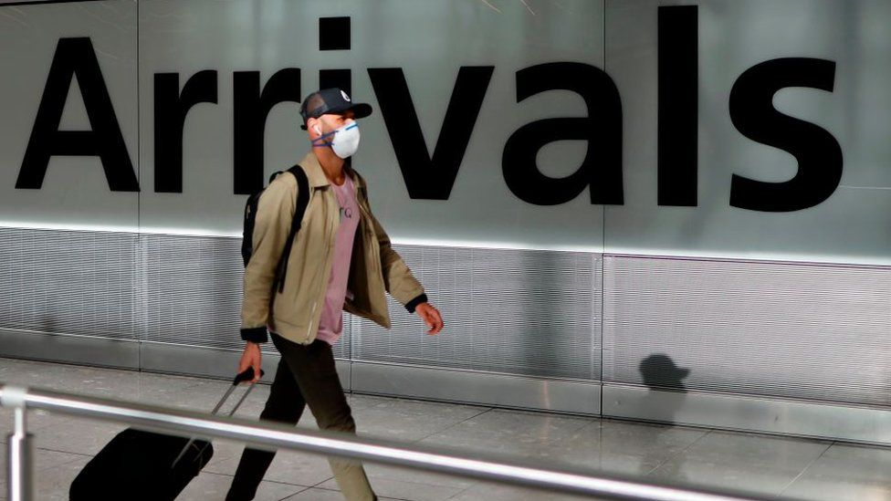 A man wearing a mask pulls his suitcase through an airport