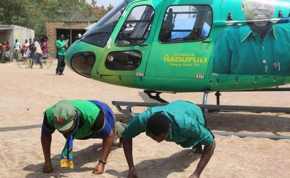 CCM politicians doing press-ups in front of a helicopter