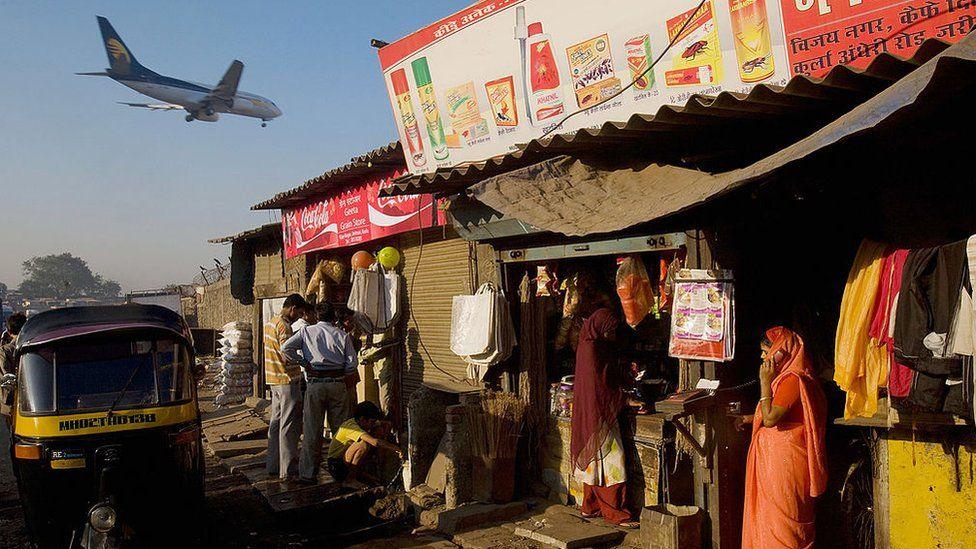 A woman talks on her cell phone as a passenger jet flies over the Jari Mari slum before landing at Mumbai Airport, on February 3, 2009 in Mumbai, India.