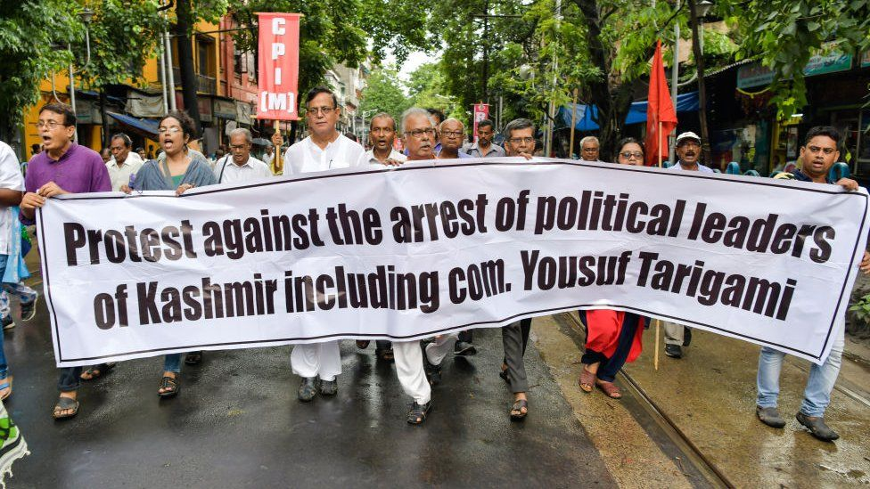 Members of the Left Front parties march with a banner during a protest rally against scrapping of Article 370 in Kolkata
