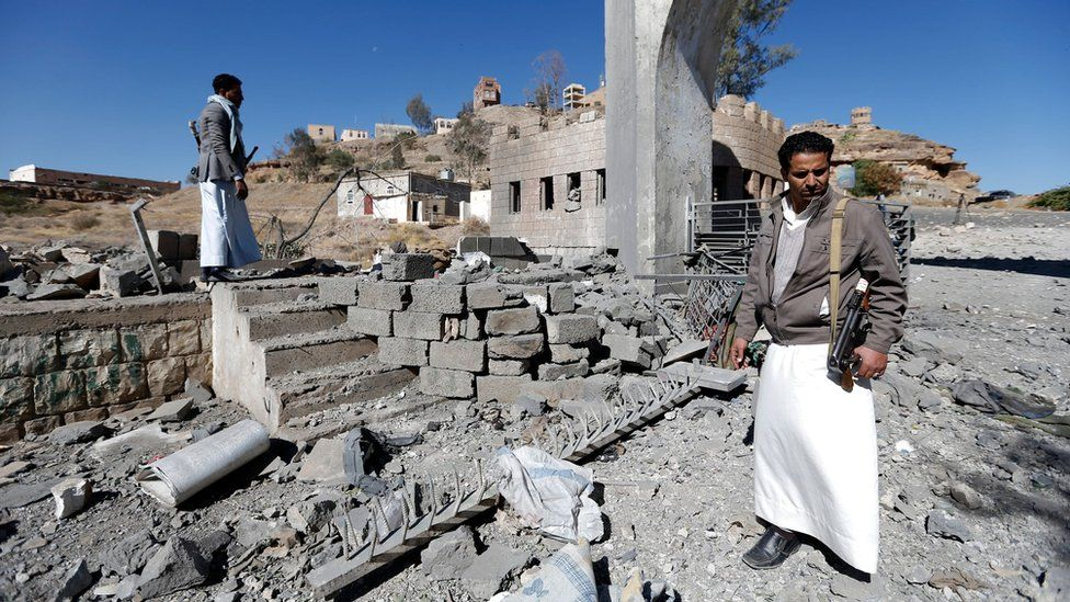 Yemeni men inspect damage caused by a reported Saudi-led coalition air strike on a rebel-controlled TV station in Sanaa (9 December 2017)