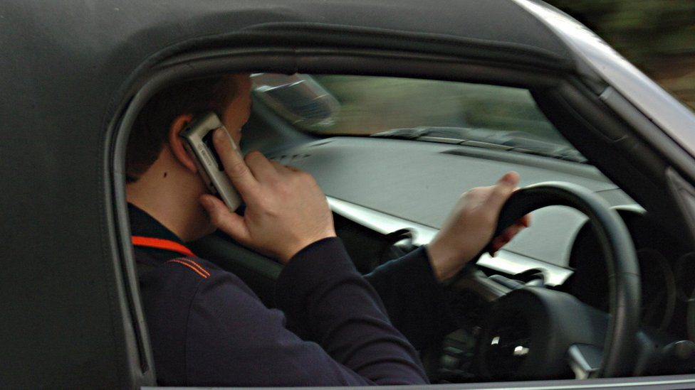 Man using his phone while driving