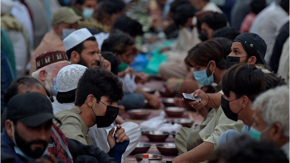 Мусульманские преданные прерывают свой ифтар на дороге во время священного месяца Рамадан в Равалпинди 28 апреля 2021 года.