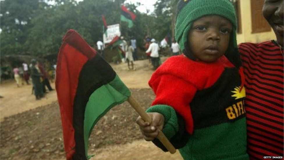 Lucia Ihim carries her nine-month-old sibbling Chidera Ihim, wearing Biafran colors, 19 August 2005 during a rally by the Movement for the Actualisation of Sovereign State of Biafra in Okwe in southeastern Nigeria.