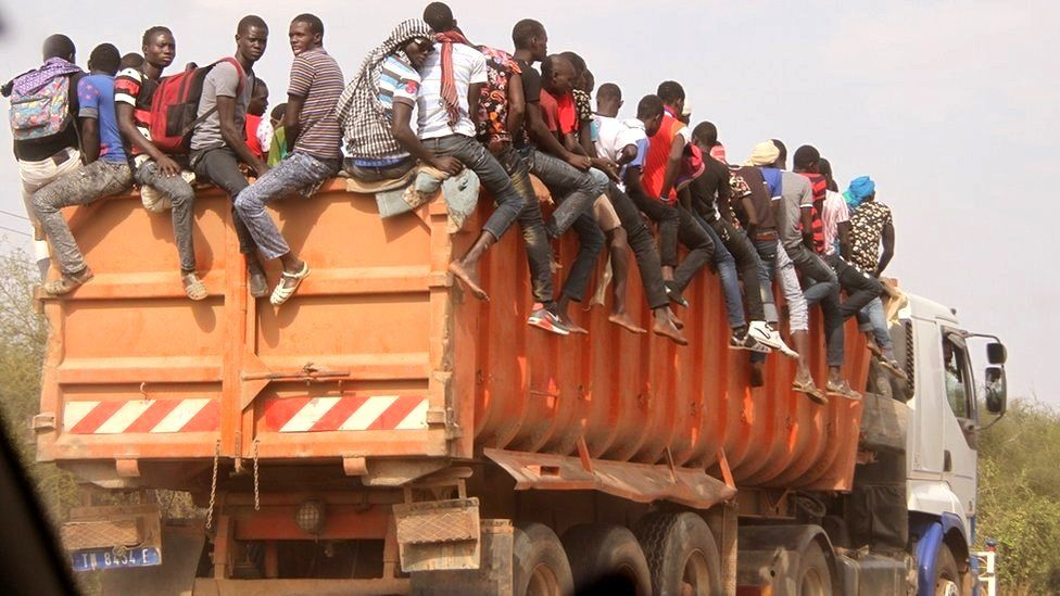 Men sitting on top of a lorry