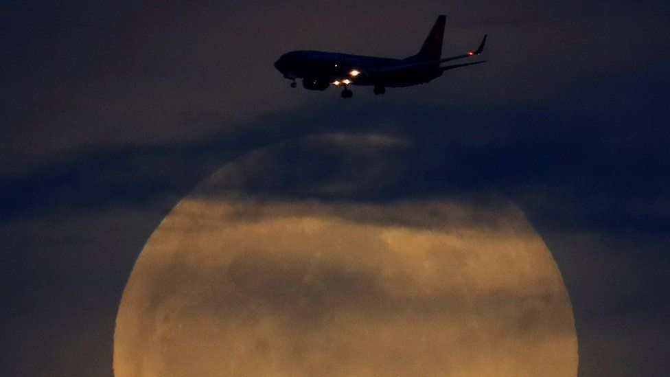 "A full moon rises between clouds as a landing commercial jet approaches the airport before the start of a total lunar eclipse that is called a ""Super Blood Wolf Moon"" in San Diego, California"