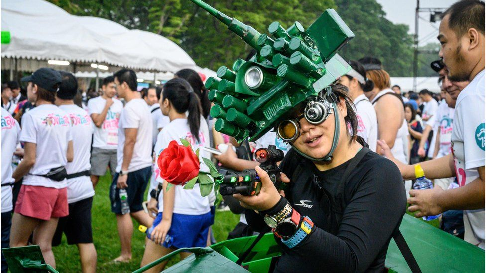 """A woman in a tank costume poses before a """"run against dictatorship"""" in Bangkok"""