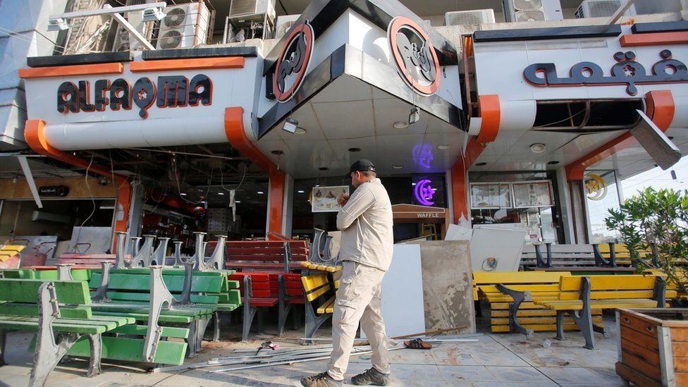 An Iraqi man inspects the site of a car bomb exploded near a cafe in Baghdad. May 30, 2017