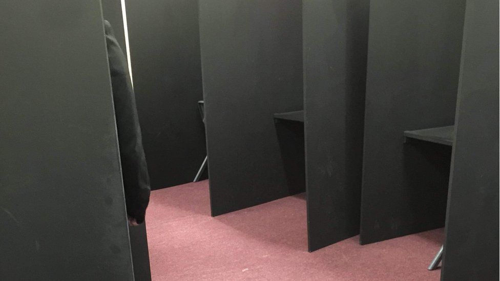 A pupil sitting in an isolation booth
