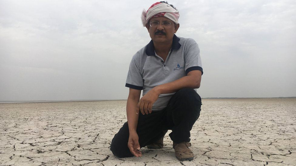Indian man in turban kneels down on cracked earth covered in a thick layer of white salt