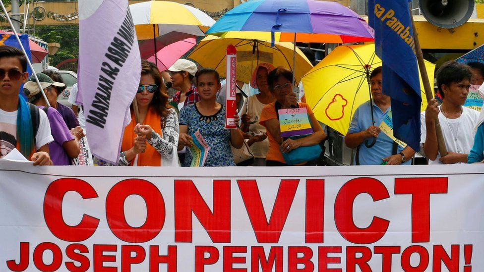 Protesters display placards during a rally near the Presidential Palace in Manila to await the verdict for U.S. Marine Pfc. Joseph Scott Pemberton who is accused in the killing of Filipino transgender Jennifer Laude, Tuesday, Dec. 1, 2015 in the Philippines