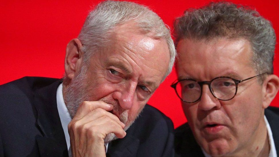 Jeremy Corbyn and Tom Watson sit together on stage at the annual Labour Party Conference in Liverpool