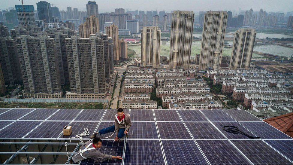 Men work on a solar panel project in Wuhan, China.