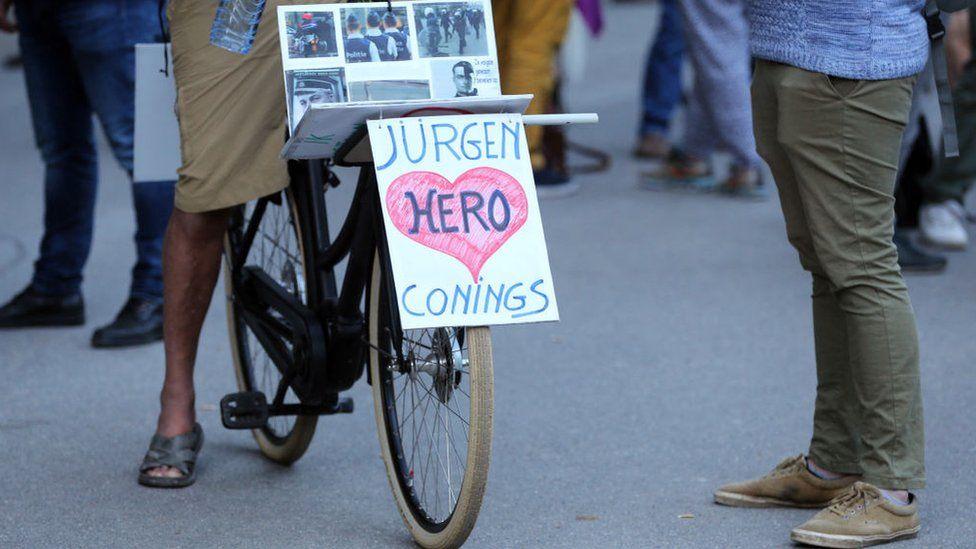 Um ciclista anda de bicicleta com uma faixa em apoio ao soldado belga de extrema direita Jürgen Conings em 29 de maio