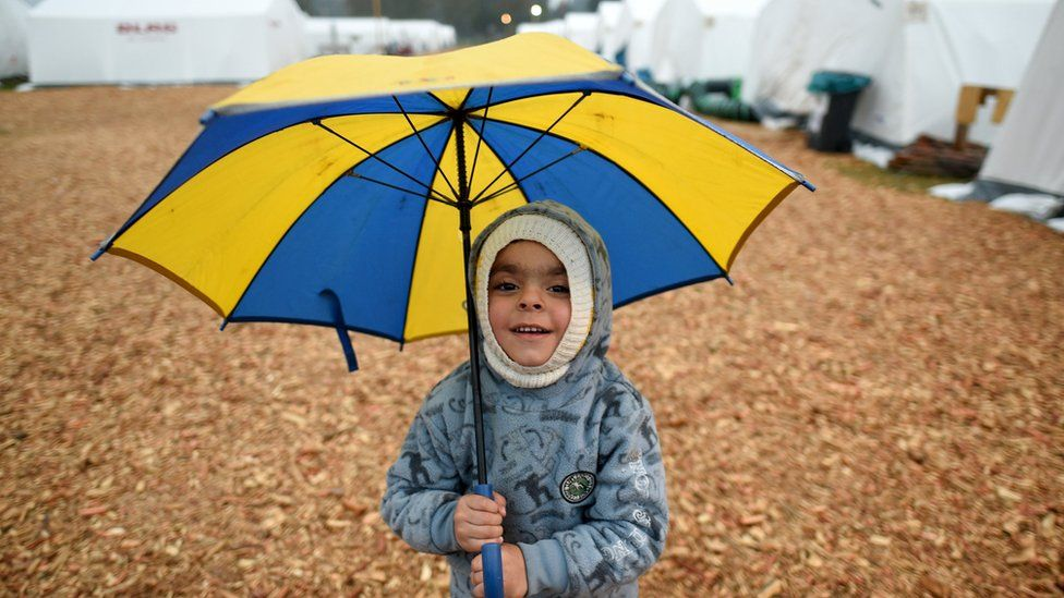 Syrian refugee boy holds an umbrella at a refugee camp in Celle, Lower-Saxony, Germany (15 October 2015)