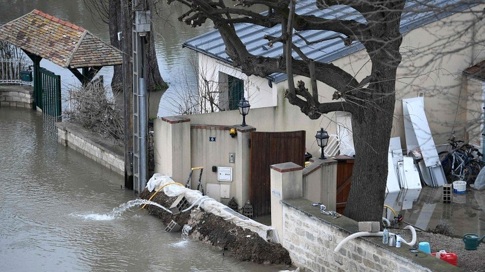 A photo taken on 29 January 2018 shows a barrier erected in front of a house to block floodwater from the Seine river (L) in Bougival, west of Paris
