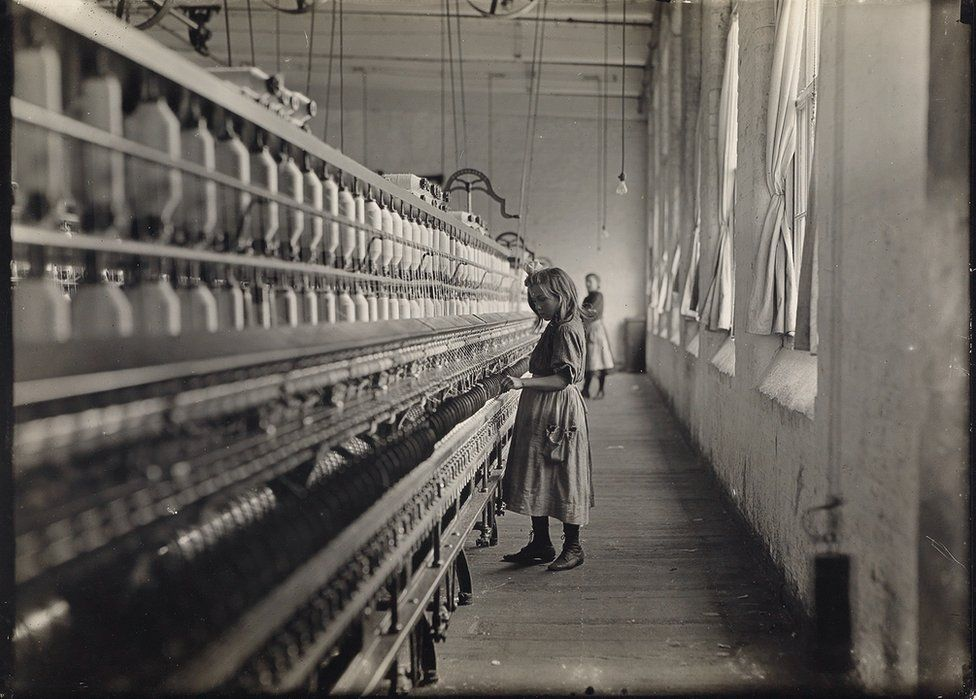 A small girl working at a mill.