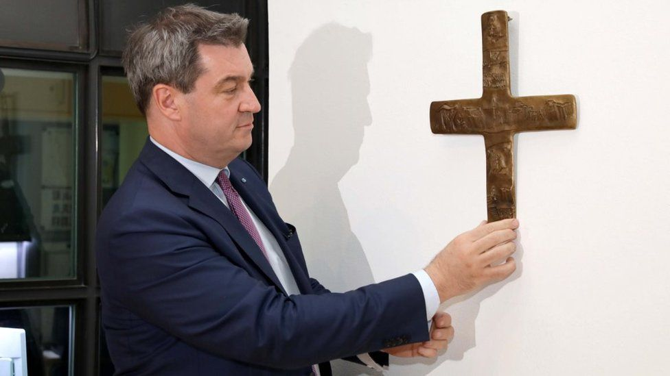 Bavaria's Premier Markus Söder places a cross in the lobby of the state chancellery in Munich