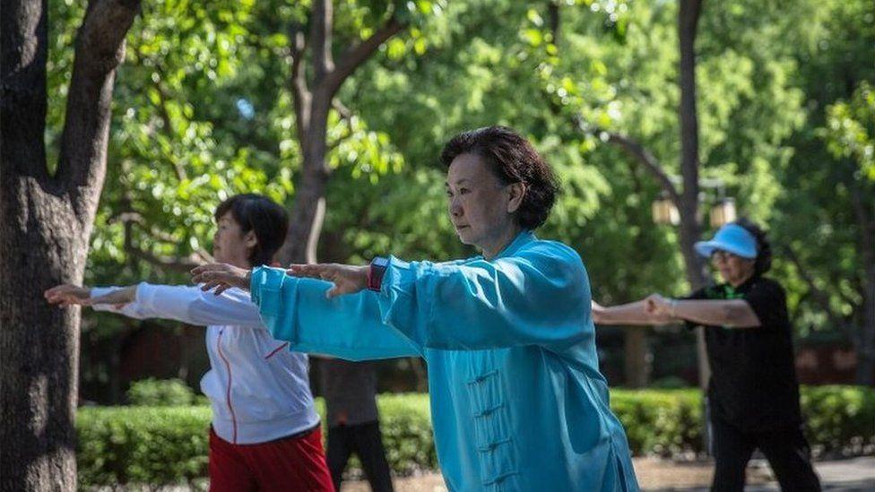 Chinese ladies practise tai chi in parks.