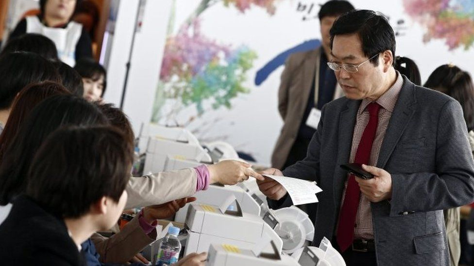 A South Korean man receives his ballot to cast at polling station in Seoul (08 April 2016)