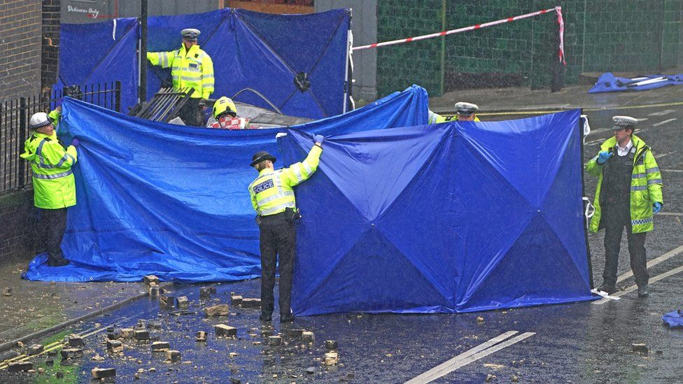 Police officers erect tarpaulin