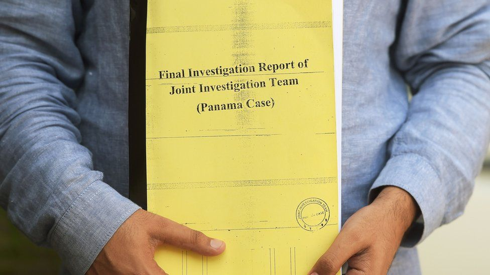A Pakistani journalist poses for a photograph with a copy of a corruption report released by a Joint Investigation Team (JIT) in Islamabad on 12 July 2017