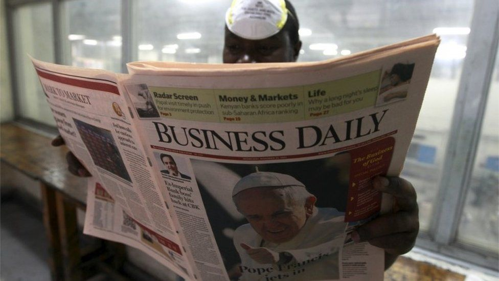 """A supervisor checks the quality of a copy of the Business Daily newspaper, with an image of Pope Francis on its front page, produced by the Nation Media Group at a printing press plant on the outskirts of Kenya""""s capital Nairobi, November 24, 2015"""