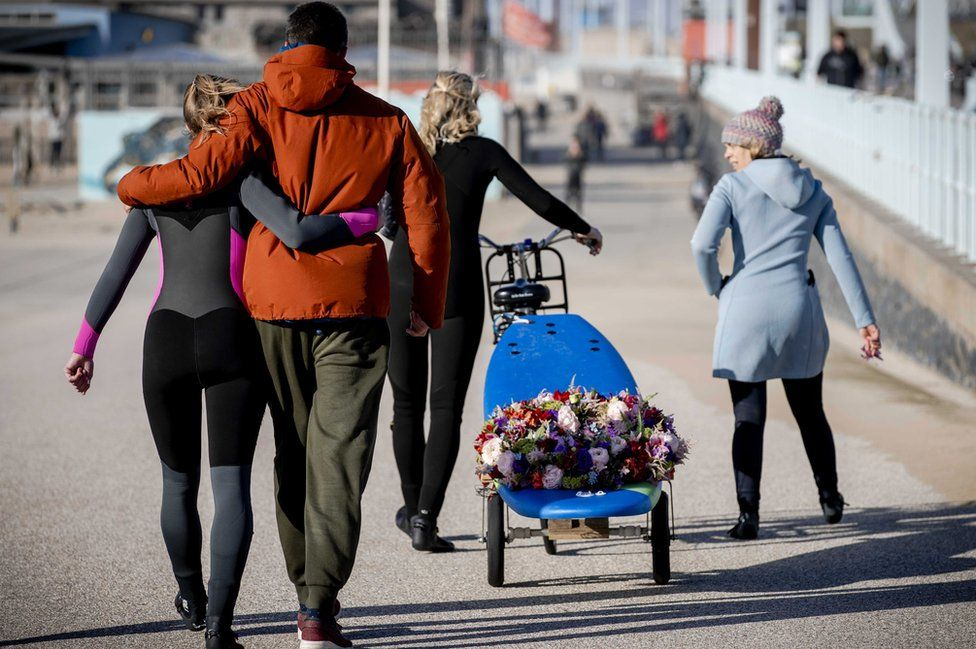 """Surfers arrive with a wreath on a surfboard at the surf club """"The Shore"""" to commemorate the deceased surfers"""
