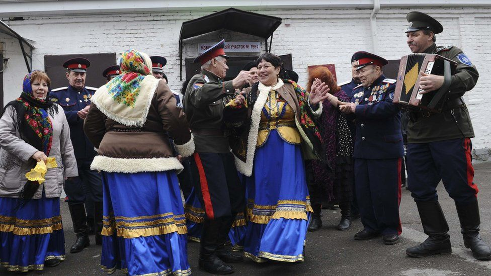 Members of a local Cossack community dance outside a polling station during the presidential election in Rostov-on-Don