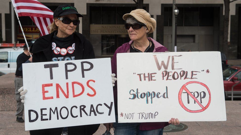 People hold signs as they demonstrate against the Trans-Pacific Partnership (TPP) trade agreement