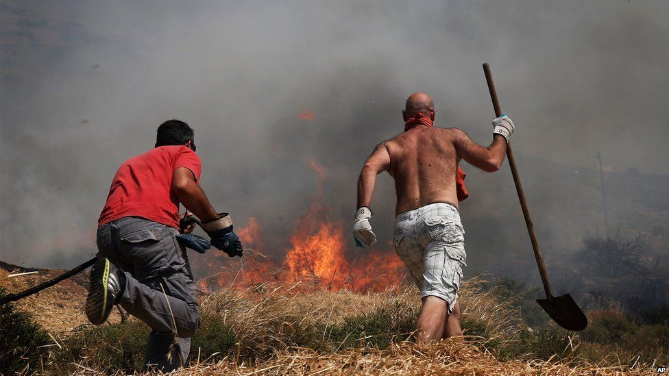 Municipality workers try to extinguish flames burning on Mount Hymettus in Athens on Friday