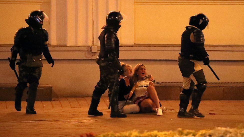 Riot police pass by two crying women during a protest the day after the presidential election, in Minsk, Belarus, 10 August 2020.