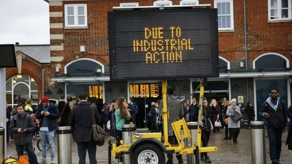 Commuters wait outside Clapham Junction during a tube strike in London