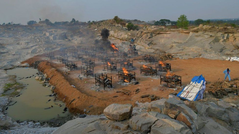 Burning pyres of the victims who died of Covid-19 coronavirus are pictured at an open air crematorium set up for the coronavirus victims inside a defunct granite quarry on the outskirts of Bangalore on May 1, 2021