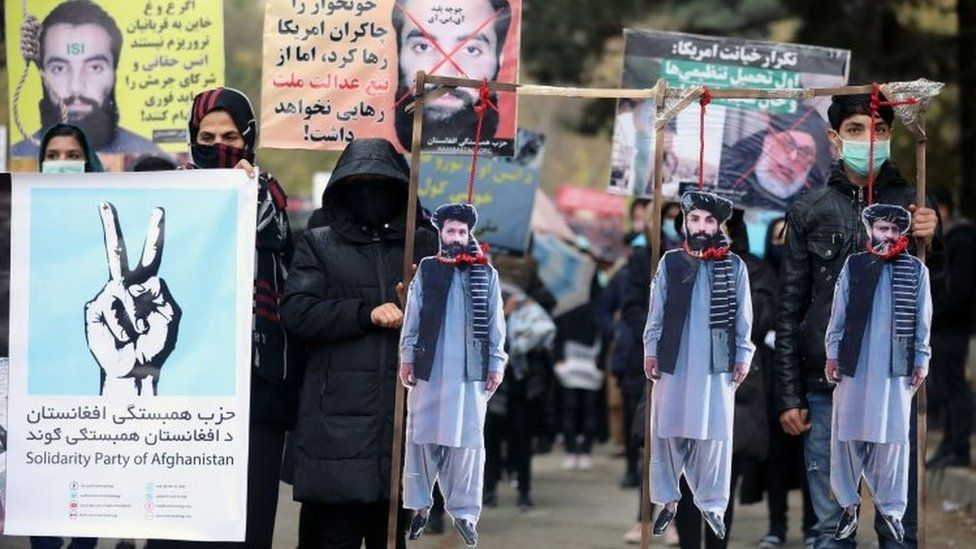 Afghan protesters carry the hanged effigies of freed prisoners Hanas Haqqani (C) and two other key Taliban key members as they shout slogans during a protest in Kabul, Afghanistan