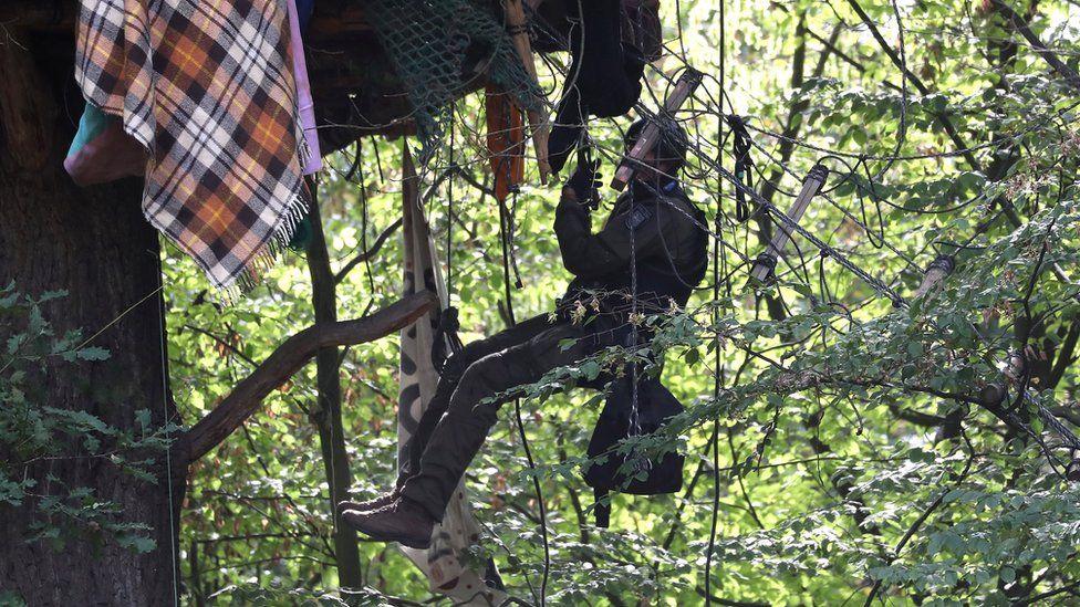 A German elite police unit member climbs a tree